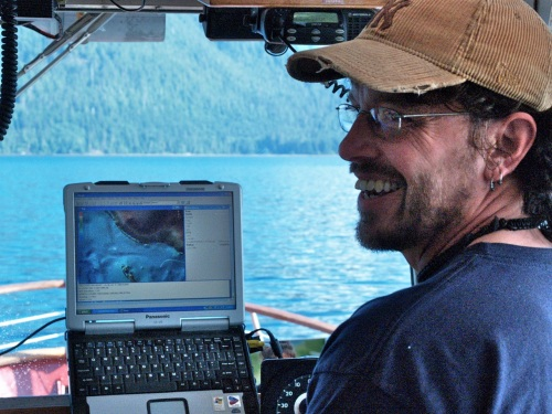 Danny Robertson positions the  Parks Canada Vessel Gwaii Haanas II above an archaeological potential model of the sea floor to enable bucket sampling.