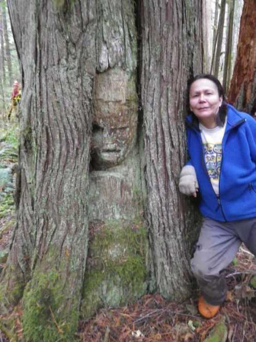 Dawn Cramer alongside the arborglyph, Nimpkish Valley. Note the healing lobes encroaching on the carving.  Photo courtesy of 'Namgis Nation via Jim Stafford.