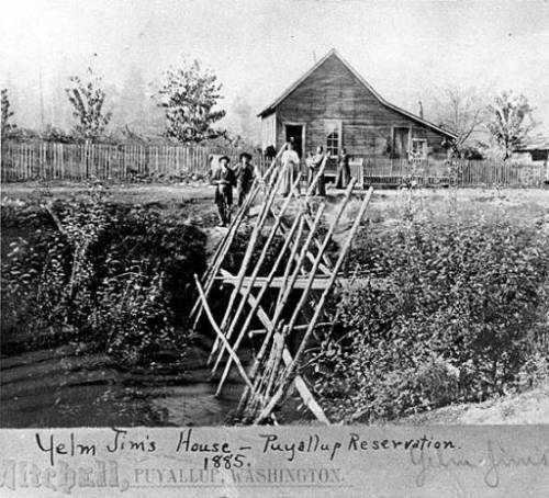 """ House belonging to survivor of the Puget Sound Indian War, Yelm Jim [Wa-he-lut or Wahoolit], seen from across the water. Two men, three women pose in front of fenced house; in foreground is a large fish trap ."" Source: http://digitalcollections.lib.washington.edu/cdm/ref/collection/loc/id/2092"