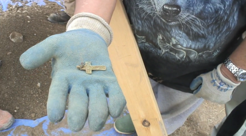 Cross found at the disturbed burial site.  Screenshot from Vimeo.