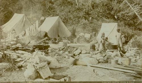 "Oversized cabinet card labeled ""Camp of Auk Indians, Alaska,"" by Winter & Pond, 1896. Image purportedly shows an Auk'w Kwáan fishing camp with tents, gear, and Tlingit people. SHI Archive, http://goo.gl/Q30Rv9"