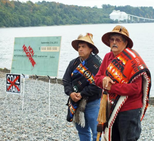 Lummi Nation then-Chair Cliff Cultee (left) and Hereditary Chair Bill James with the check they will burn at Cherry Point. Photo: Floyd McKay Source: Crosscut.com