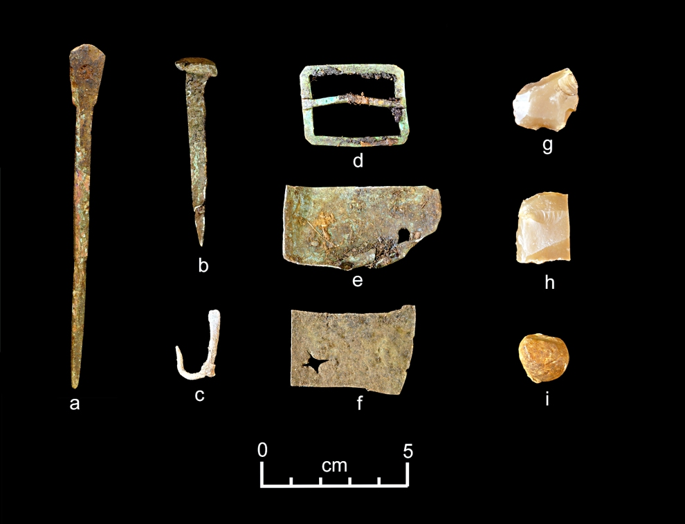 A representative collection of artifacts discovered in July 2015 includes (from left) part of a set of dividers, a nail, a fishhook, a buckle, sheet copper, gun flints and a musket ball. Credit: Dave McMahan, Sitka Historical Society via NSF