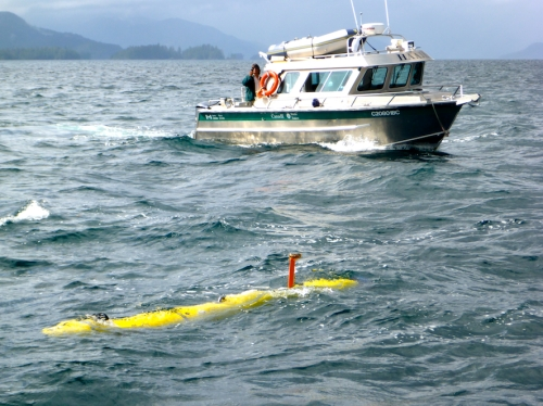 Autonomous Underwater Vehicle on surface of Juan Perez Sound, Haida Gwaii, with Parks Canada support vessel behind.